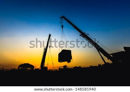 mobile crane lifting generator, silhouettes at sunset - stock photo