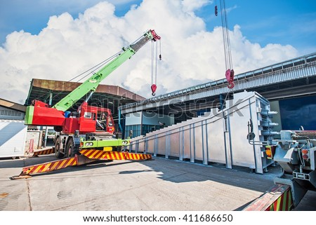 Mobile crane operating by lifting and moving an heavy electric generator - stock photo