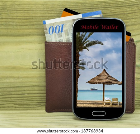 Mobile devise with wallet, money and credit card isolated on wood background  - stock photo