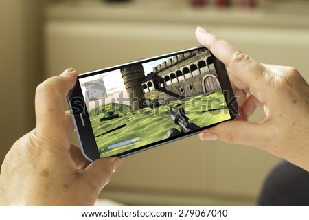 mobile gaming concept: mature woman hands with a 3d generated smartphone with game on screen - stock photo