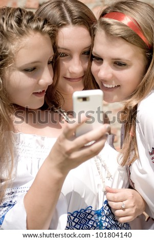 Mobile Girls Fun: portrait of excited beautiful three young women teen smiling and looking at digital device or mobile phone on brick wall background - stock photo