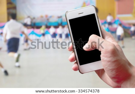 Mobile hold in hand with blur of student playing  in school - stock photo