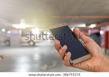 Mobile hold in hand with blur parking lot. - stock photo