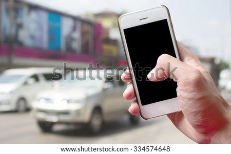 Mobile hold in hand with blur Traffic car on the road - stock photo