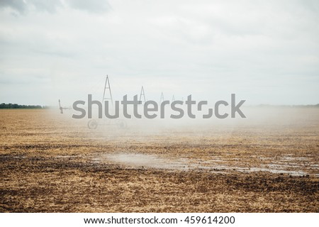 Mobile irrigation pivot watering on an empty field. Farmer watering the field after a successful harvest on a cloudy day - stock photo