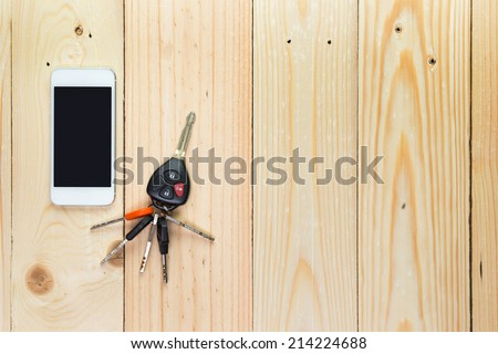 Mobile phone and car remote keys on wooden background - stock photo