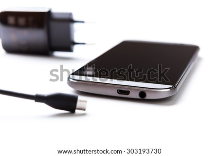 Mobile phone and charger are on the table.