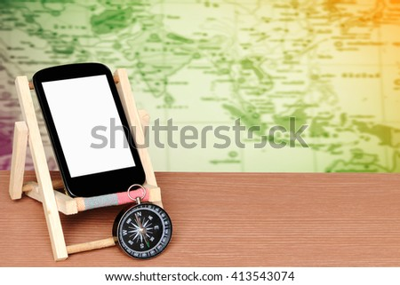 mobile phone and compass with blur part of world map,color filter tone background - stock photo