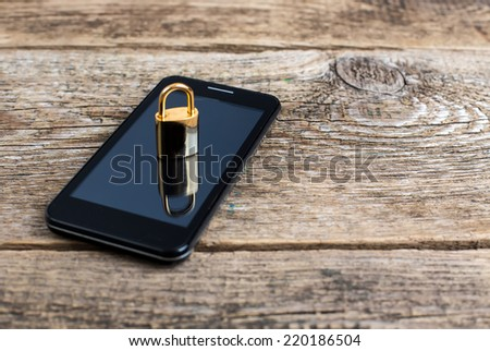 Mobile phone and lock on wooden desk - stock photo