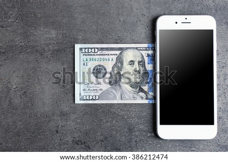 Mobile phone and money on grey background. Concept of payment and savings. - stock photo