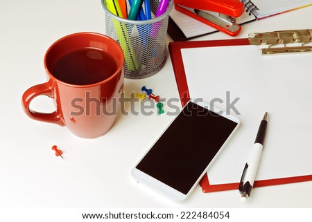 Mobile phone and office items on white tabletop. Business concept - stock photo