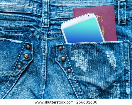 Mobile phone and  passport book in blue jeans back pocket/ traveling concept - stock photo