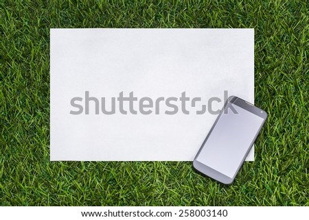 Mobile phone and sheet of paper on the green grass - stock photo