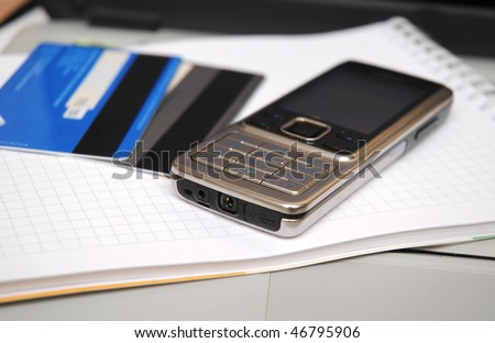mobile phone and visa cards over checked copybook