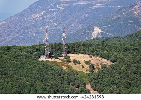 Mobile phone base station and telecommunication radio antenna towers on mountain, aerial view