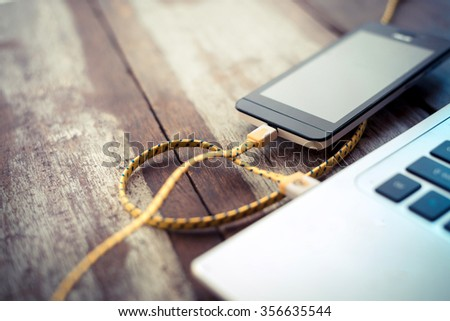 mobile phone charging from laptop usb port - stock photo