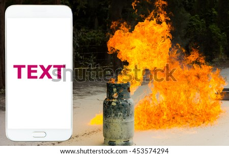 Mobile phone, gas tank fired as background. - stock photo