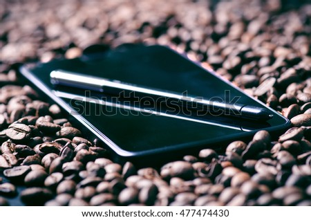 Mobile phone in a middle of coffee beans. Technology concept. Stylus pen on a smart phone