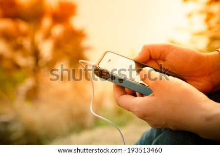 Mobile phone in a woman's hand, sunset - stock photo