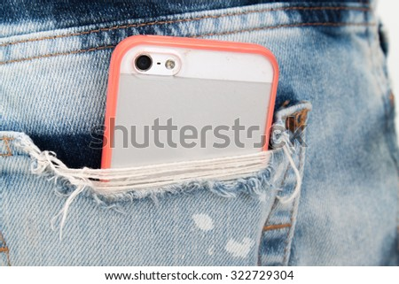 mobile phone in pocket with pink color case. - stock photo