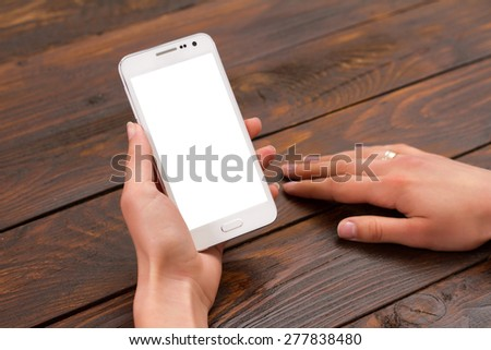 Mobile phone in the hands of a girl with a blank screen - stock photo
