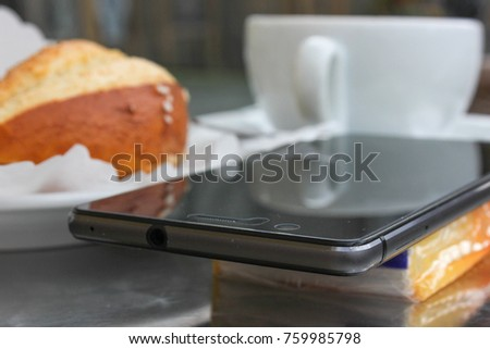 mobile phone next to an italian cappuccino with german pretzel with chocolate artwork on creme of coffee on metal table top in south german historical city near munich and stuttgart