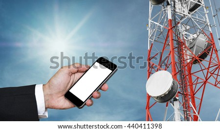 Mobile phone on hand with copy space, and telecommunication tower with satellite dish telecom network on blue sky with sun - stock photo
