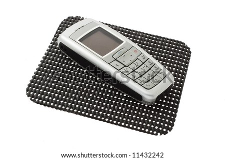 Mobile phone on tabletop non slip mat isolated on white background