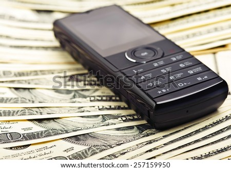 mobile phone on the money background - stock photo