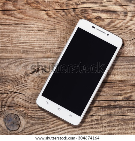 Mobile phone on the old board table. - stock photo