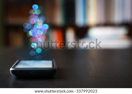 Mobile phone on the table against the background of written books. Shallow depth of field.