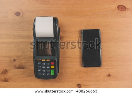 Mobile phone payment in shops with nfc system. Detail of POS and mobile. Top view