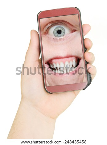 Mobile phone with eye and teeth. Big Brother is watching you. Internet safety concept. - stock photo