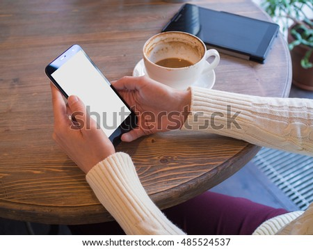 Mobile phone with isolated screen for your information. Woman reads the news on the phone sitting in a cafe for a wooden table and finishing off a delicious coffee