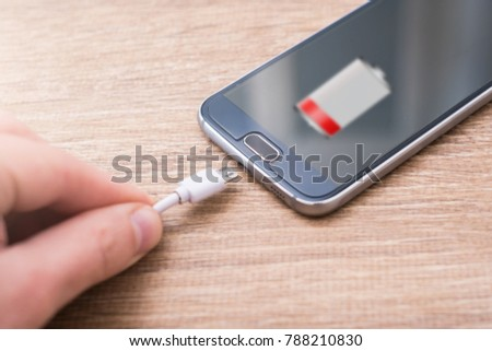 Mobile phone with low battery symbol on the screen on a wooden desk