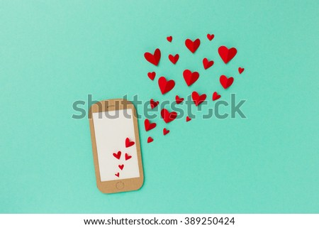 Mobile phone with red hearts flying from the screen - paper illustration image concept for online dating, dating apps - stock photo