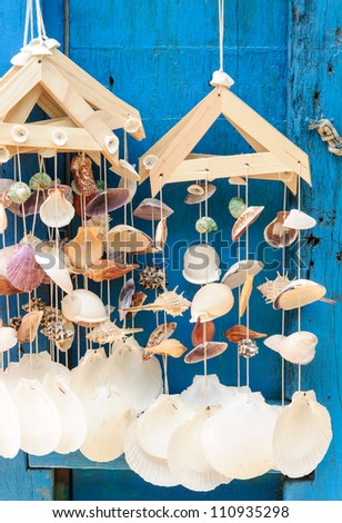 Mobile sea shell hanging on the blue door. - stock photo