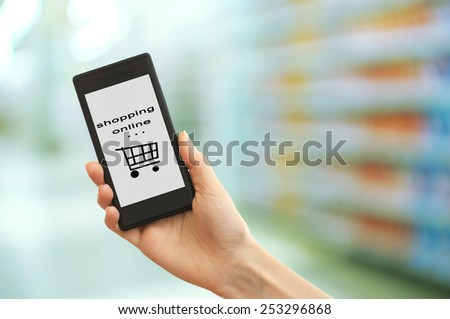 Mobile shopping concept. Hand holding mobile phone for internet shopping on supermarket background - stock photo