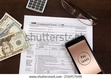 Mobile tax filing - 1040 forms with cell phone and calculator - stock photo