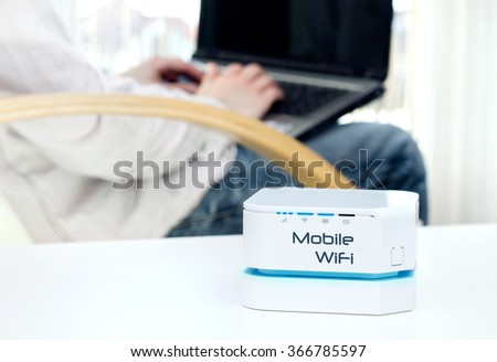 Mobile WiFi router device on the table and businessman resting on armchair in background