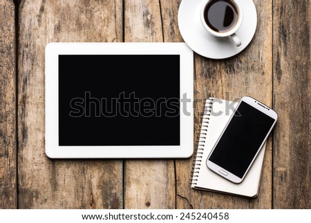 Mobile workplace with tablet PC, phone and cup of coffee on rustic wooden table. Top view image - stock photo