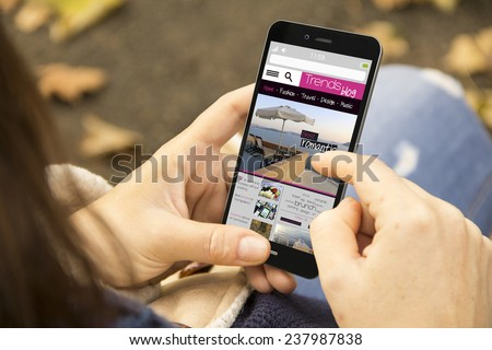 mobility and modern lifestyle concept: young woman reading a trends blog at the park - stock photo