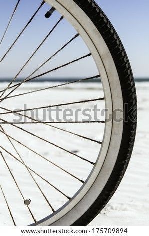 Mobility at the beach: Focus on front tire of bicycle, with horizon of Atlantic Ocean in background (shallow depth of field) - stock photo