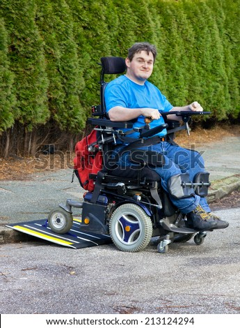 Mobility for infantile cerebral palsy patients caused by birth complications with a spastic young man in multifunctional wheelchair negotiating a mobile ramp on a kurbside during integration outing - stock photo