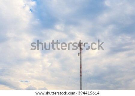 moblie phone antenna post under white cloud - stock photo