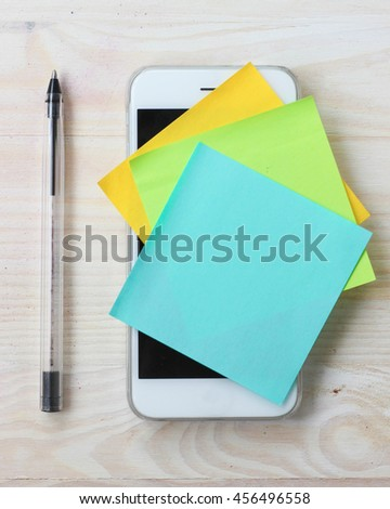 Moblie phone reminder notes. Paper sticky notes and black pen on smart phone. - stock photo
