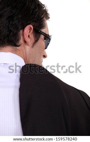 Mobster carrying his jacket - stock photo