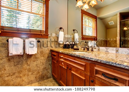 Mocha tile wall trim bathroom with brown cabinets and mirror