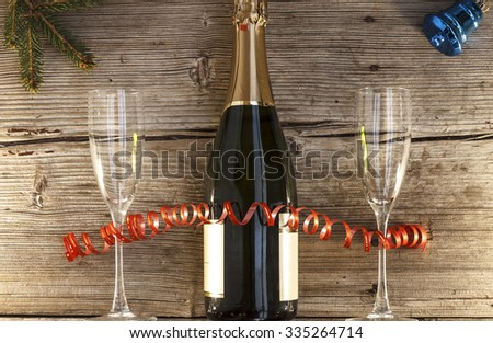 Mock Up. Christmas, New Year, Celebration, Champagne in a glass bottle, two glasses of wine, tree, bells, streamers, Top view, closeup. - stock photo