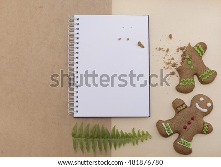 Mock up decorated Christmas gingerbread biscuits and blank notepad with craft paper background